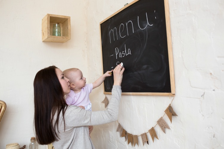 Mom and Toddler Daughter playing menu planning to write to the blackboard and chalk, lifestyle real interior